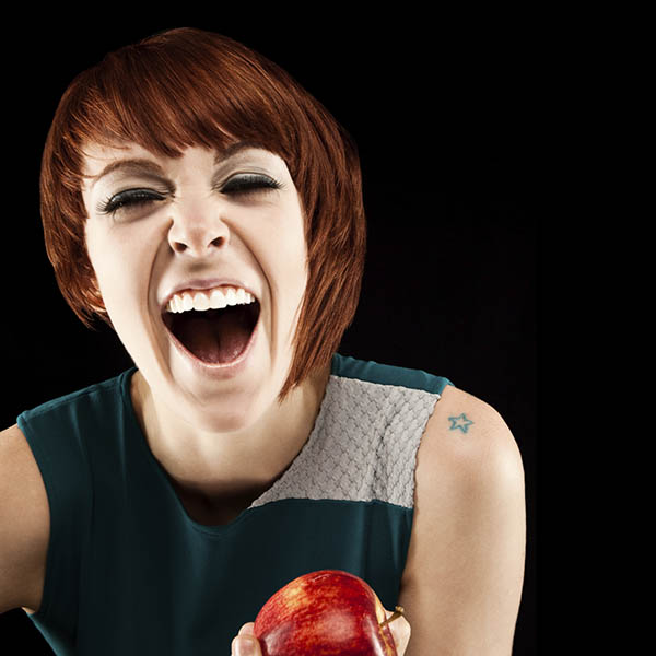 An attractive young woman is holding an apple and has her mouth open laughing. Her eyes are closed. Square format. Isolated on black.